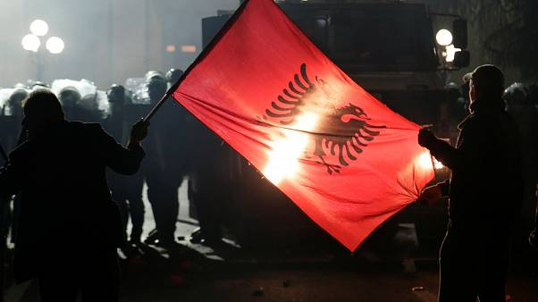 Anti-government supporters hold an Albanian flag in front of police during a protest in Tirana