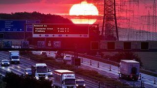 A felkelő napkorong fénye világít be egy autópályát Frankfurt közelében 2019. június 5-én