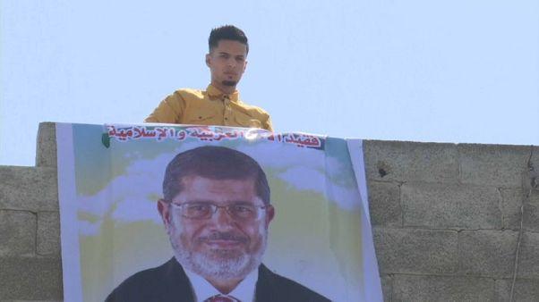 شاب يقوم بتعليق صورة كبيرة لرئيس مصر السابق محمد مرسي على حافة بناء في رفح بقطاع غزة