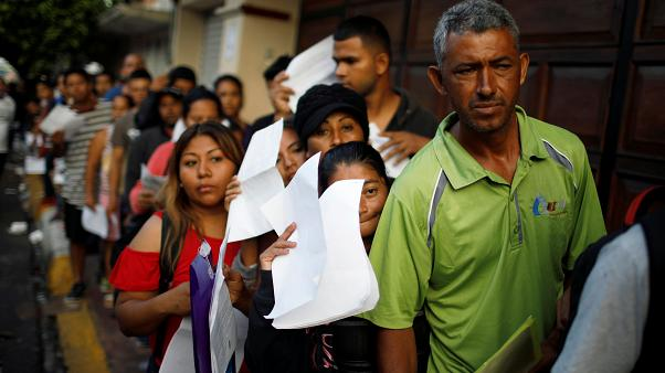 Cuban migrants wait outside the Mexican Commission for Refugee Assistance (COMAR) in Tapachula