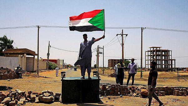 متظاهر سوداني يرفع العلم الوطني في الخرطوم يوم 5 يونيو حزيران 2019