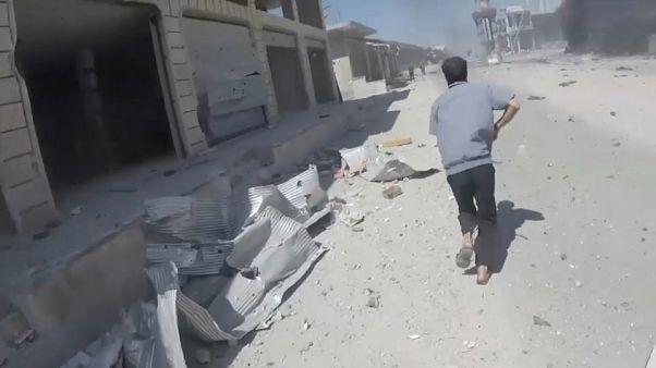 أحد المدنيين يركض قرب بلدة معرة النعمان بعد قصف جوي عنيف للإنقاذ أو العثور على الضحايا