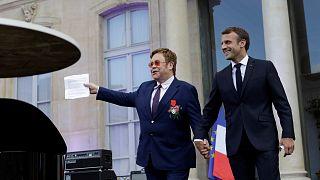Sir Elton John és Emmanuel Macron francia elnök kézenfogva az Élysée-palota előtt