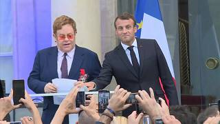 الرئيس الفرنسي إيمانويل ماكرون والنجم إلتون جون