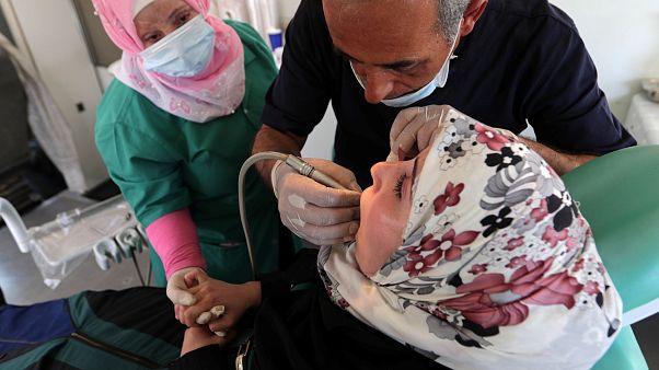 طبيب الأسنان باسل معراوي يعتني بمريضة في عيادة متنقلة في شاحنة بالقرب من أعزاز