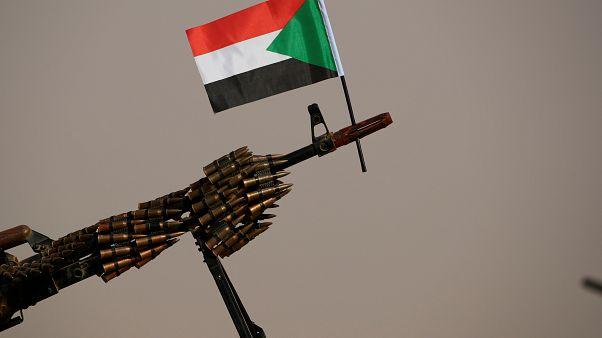 """علم السودان مرفوع على فوهة بندقية آلية لقوات الدعم السريع """"الجنجويد"""". حزيران/2019"""