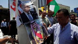 A Palestinian demonstrator burns posters depicting Bahrain's King Hamad bin Isa Al Khalifa and U.S. President Donald Trump during a protest against the Bahrain conference