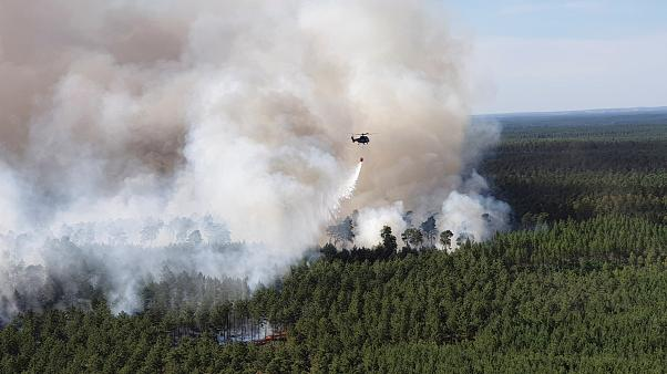 A German Federal Police helicopter carries water to extinguish forest fire near Lieberoser Heide in eastern Germany, June 25, 2019.