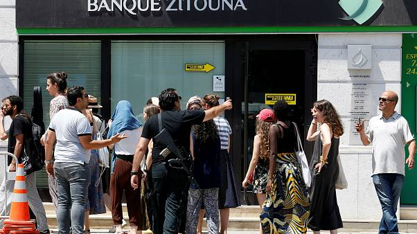 عنصر من الشرطة التونسية يطالب سياحا بالابتعاد عن أحد مكان التفجيرين بتونس العاصمة. حزيران/2019