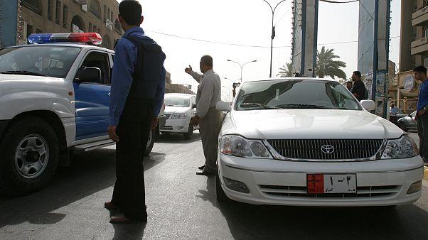 رجل أمن عراقي يحرس سيارة تابعة لسفارة البحرين في بغداد بعد إطلاق النار على دبلوماسي بحريني. تموز/2005