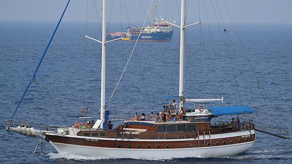 Veleiro com turistas a navegar ao largo de Lampedusa não muito longe do barco de socorro a migrantes
