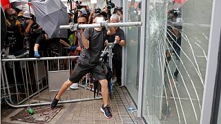 A protester smashes a window at the Legislative Council building