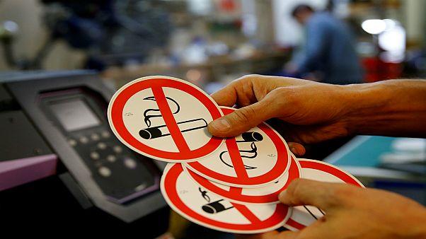 """موظف يُظهر لافتات """"ممنوع التدخين"""" في ورشة الطباعة في فيينا/ النمسا 2018"""