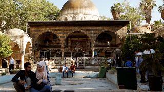 People sit near the Ottoman-era Tekkiye Suleimaniye mosque complex in Damascus, Syria