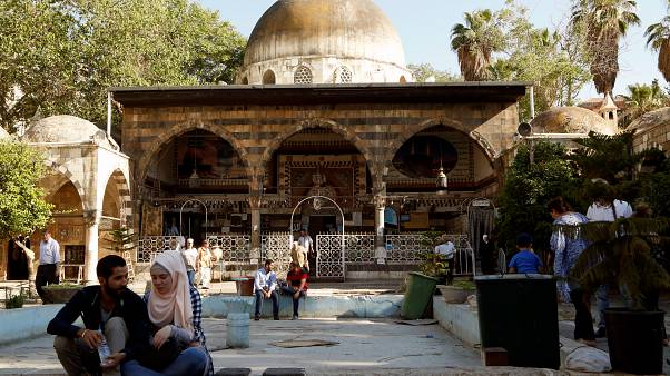 People sit near the Ottoman-era Tekkiye Suleimaniye mosque complex in Damascus, Syria
