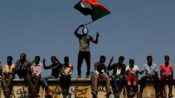 FILE PHOTO: A Sudanese protester wearing a Guy Fawkes mask waves a national flag outside the Defense Ministry compound in Khartoum