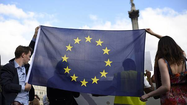 شاب وشابة يحملان علم الاتحاد الأوروبي في وسط العاصمة البريطانية لندن. حزيران 2016