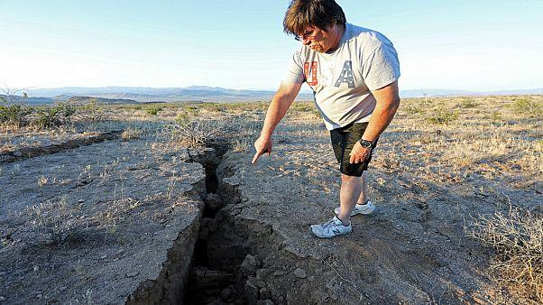رجل يشير إلى أخدود في الأرض أحدث جراء زلزال جنوبي كاليفورنيا