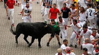 Revellers attempt to dodge a bull during the first running of the bulls at the San Fermin festival in Pamplona, Spain, July 7, 2019.