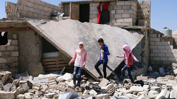 لاجئون سوريون بجانب بيت مهدم في لبنان