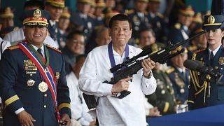 رئيس الفلبين رودريجو دوتيرتي يحمل بندقية قنص خلال حفل بمعسكر في مانيلا - بصورة من أرشيف رويترز