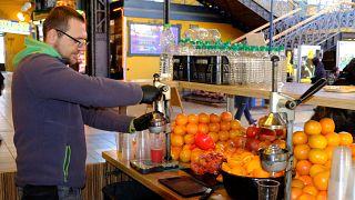Narancsból, grapefruitból és gránátalmából préselt üdítőitalokat árul egy férfi a Fővám téri Vásárcsarnokban.