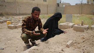 رجل يمني وزوجته يصليان على روح فقيدهما