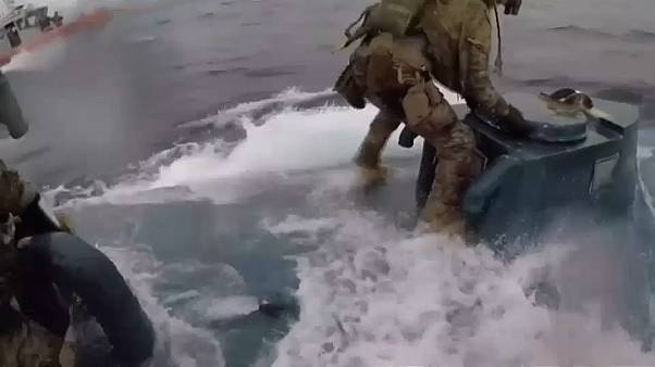 عنصر تابع لخفر السواحل الأميركي يحاول فتح باب القارب الغوّاص
