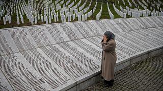 Una mujer reza cerca de la placa conmemorativa con nombres de fallecidos en la masacre de Srebrenica, antes de ver el juicio en el tribunal de La Haya, en Potocari.