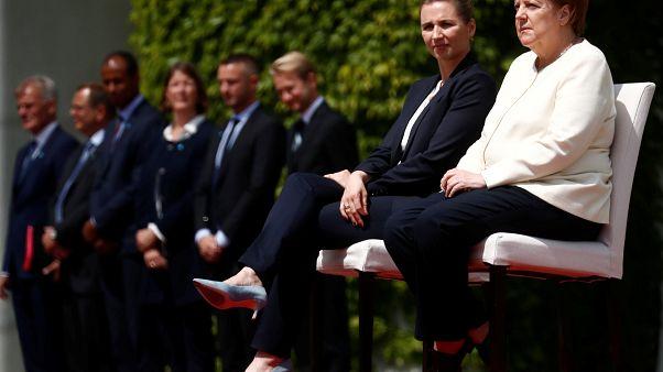 في مخالفة للبروتوكول، جلست ميركل بجانب رئيسة وزراء الدنمارك، ميتيه فريدريكسن، خلال تأدية النشيدين الوطنييْن