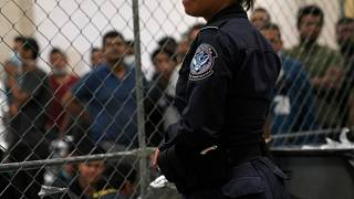 Single men wait behind caged wire at a detention facility in Texas on Friday