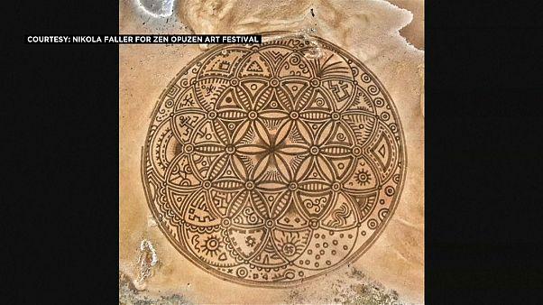 شاهد: فنان كرواتي يرسم أشكالاً هندسية رائعة وبالغة التعقيد على الرمل