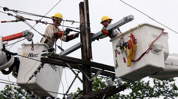 عاملان يصلحان أحد خطوط الكهرباء التي تضررت بفعل العاصفة باري في نيو أورليانز بولاية لويزيانا الأمريكية يوم الاحد