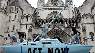 """Una singolare forma di protesta: una barca azzurra con scritto """"Act Now"""" davanti alla Corte di Giustizia di Londra. (15.7.2019)."""