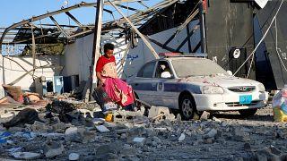 A Tripoli melletti lebombázott menekülttáborban gyűjt ruhákat egy migráns