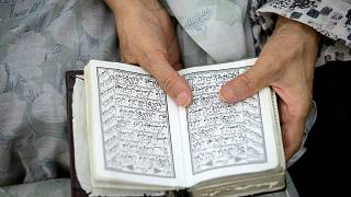 A woman prays while holding the Quran.