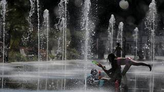 FILE PHOTO: People cool off in a fountain in Nice as a heatwave hits much of the country, France