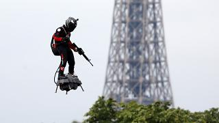 Franky Zapata flies on a Flyboard near the Eiffel Tower during the traditional Bastille Day military parade on the Champs-Elysees Avenue in Paris