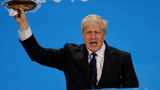 Boris Johnson holds a plastic wrapped kipper fish during a hustings event in London, Britain July 17, 2019