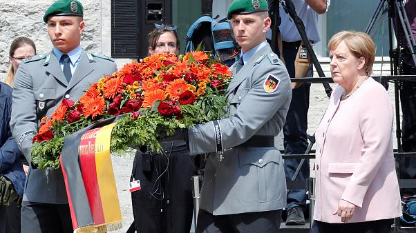 Angela Merkel stands with German soldiers laying a wreath to honour the failed plotters