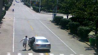رجل يمضي مسرعا محاولا إيقاف السيارة التي انسابت تسير في طريق منحدر دون سائق