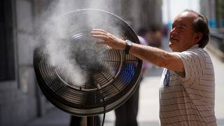 A man tries to cool himself with a fan in central Madrid, Spain, June 27, 2019.