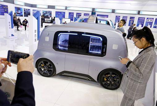 زائر يلتقط صورة لسيارة ذاتية القيادة من نيوليكس في بكين في 18 أكتوبر تشرين الأول 2018