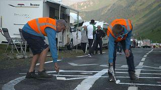 Watch: Tour de France employs men to redesign the phallic graffiti on the route