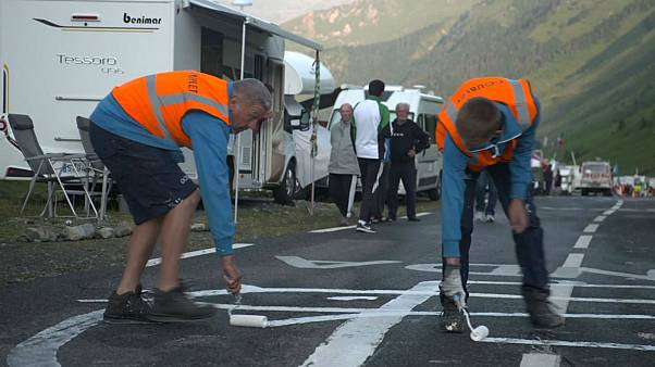 Watch: Tour de France employs men to redesign the phallic graffiti on the route