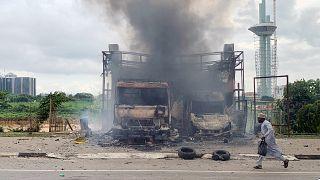 رجل يجري أمام سيارتين محترقتين عقب اشتباكات بين الشرطة النيجيرية ومجموعة من المحتجين الشيعة في العاصمة أبوجا