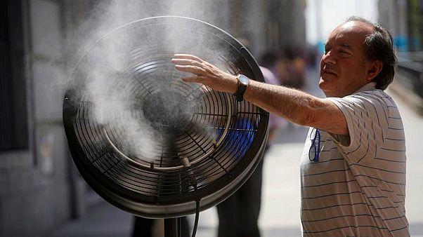 رجل يحاول الانتعاش بشيء من البرودة المنبعثة من مروحة كهربائية وسط مدريد. 27يونيو حزيران 2019. خوان مدينة/رويترز