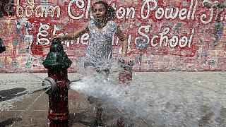A girl cools off in Washington Heights in Manhattan during a July 2019 heat wave