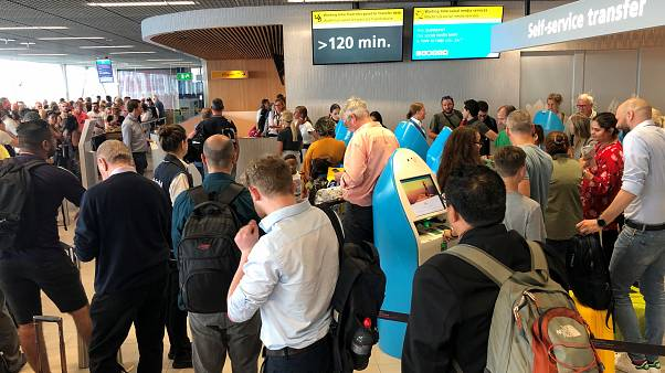 Passengers and staff wait at Amsterdam Schiphol airport during an outage at the airport's main fuel supplier that kept dozens of flights on the ground,