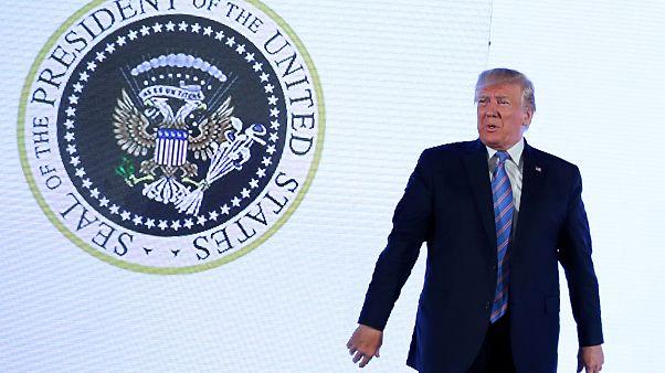 الرئيس الأمريكي دونالد ترامب أمام شعار معدّل للرئاسة الأميركية